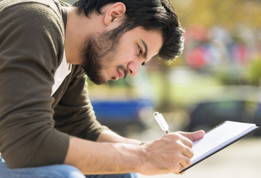S+ Close-up of a young man writing his journal outdoors. Istanbul iStockalypse 2014 Pitch Shoot.